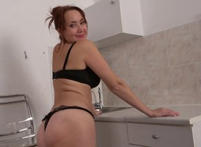 Flimsy housewife getting wet in her kitchen